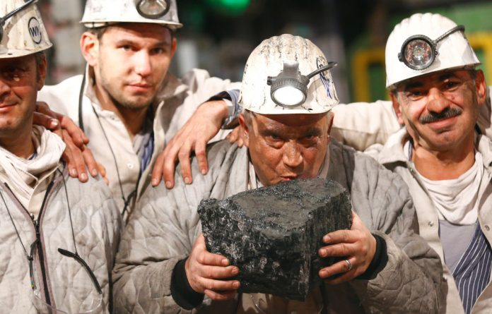 A miner kisses the symbolic last piece of stone coal harvested from the Franz Haniel shaft during a ceremony marking the closure of the last active black coal mine in Bottrop