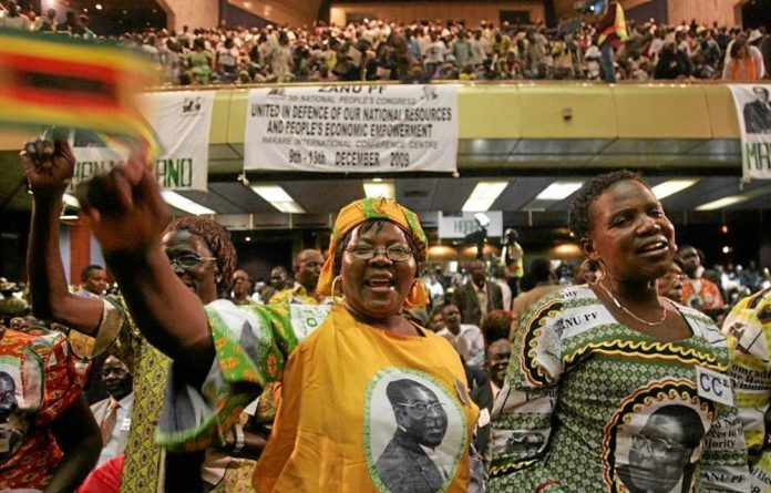 Party time: Zanu-PF supporters sing the praises of President Robert Mugabe at the organisation's 2009 conference. The president will be eulogised once again in December.