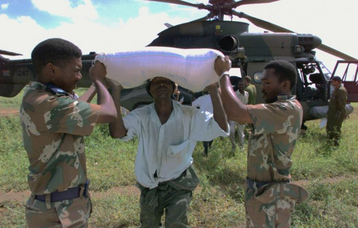 South African National Defence Force soldiers help to unload maize for flood victims in. Mozambique.