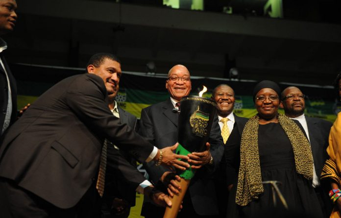President Jacob Zuma takes the centenary torch before his ANC centenary lecture in Cape Town on February 23.