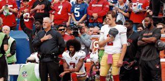 San Francisco 49ers quarterback Colin Kaepernick kneels in protest during the US anthem.