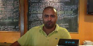 Osman Abdelmoniem mans the cash register in his hotel restaurant in Juba.
