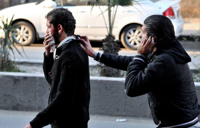 A Syrian helps a man who was injured after two cars bombs exploded