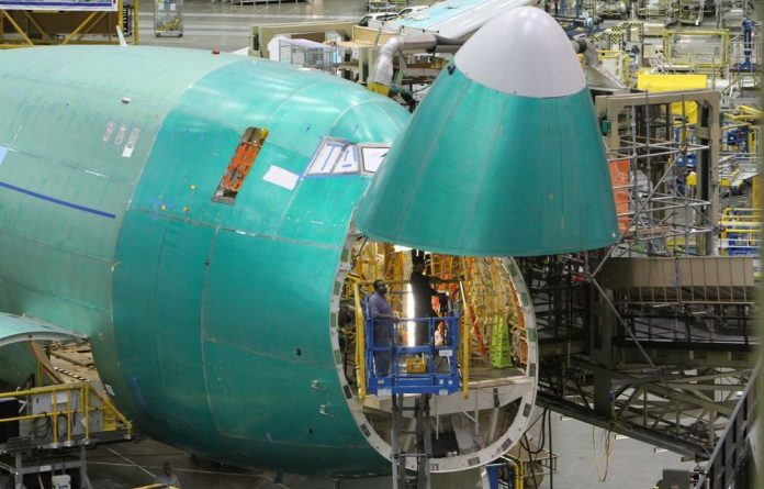 Boeing employees work inside the nose cone of a plane