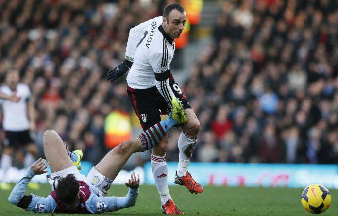 Aston Villa's Chris Herd challenges Fulham striker Dimitar Berbatov at Craven Cottage.