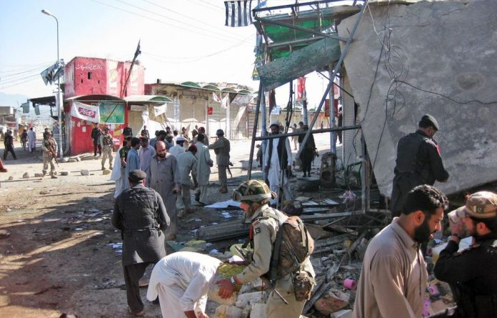 Security personnel investigate the site of a suicide bombing in the tribal region of Khar in Bajur