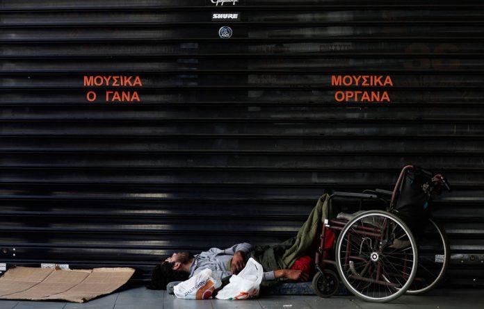 A homeless man sleeps on a sidewalk in Athens. Homelessness