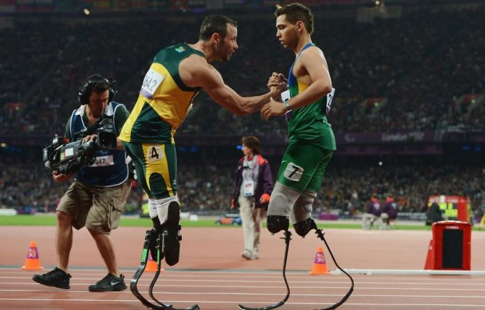 Alan Fonteles Cardoso Oliveira of Brazil is congratulated by Oscar Pistorius of South Africa after winning gold in the Men's 200m T44 Final.