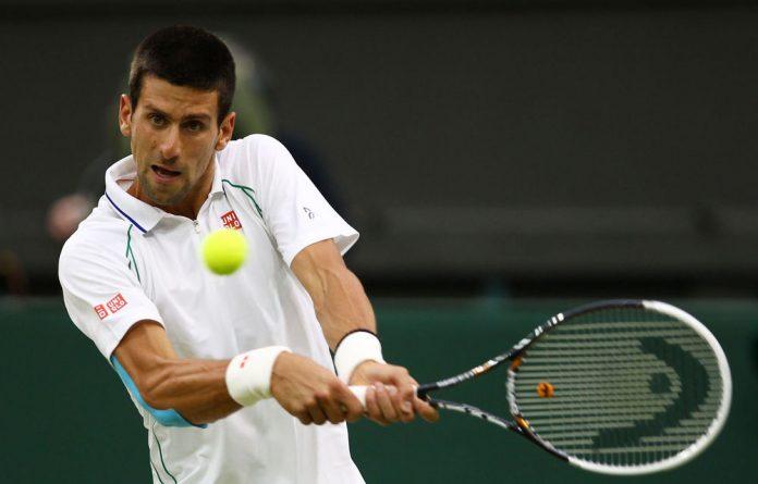 Novak Djokovic hits a backhand return during his fourth round match against Viktor Troicki on day seven of the Wimbledon  Championships.