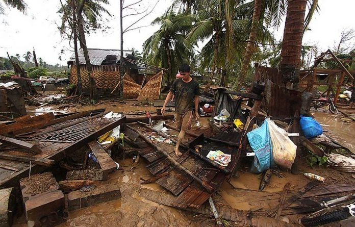 Residents walk amongst their destroyed houses after Typhoon Bopha hit Compostela town