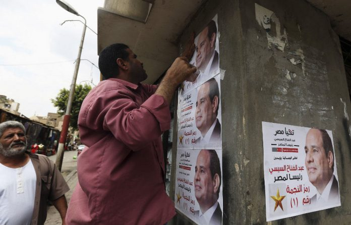 A volunteer puts up posters of Abdel Fattah al-Sisi in the El Gamaliya district in Cairo on May 9 2014.