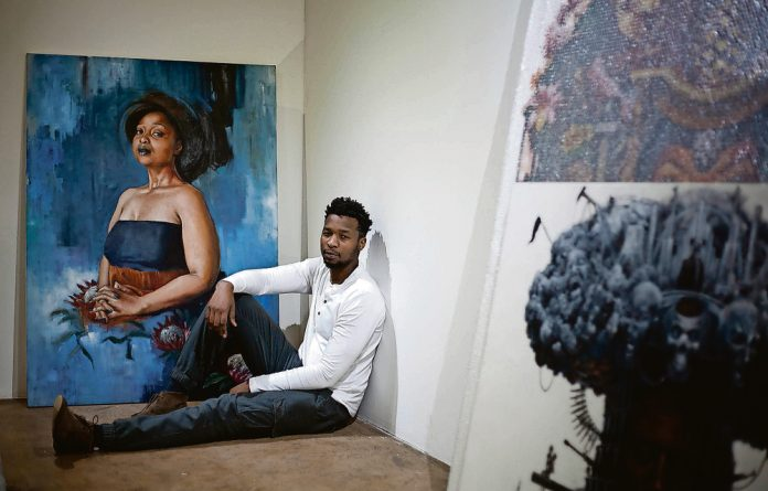 Loyiso Mkize with one of his portraits at his solo exhibition