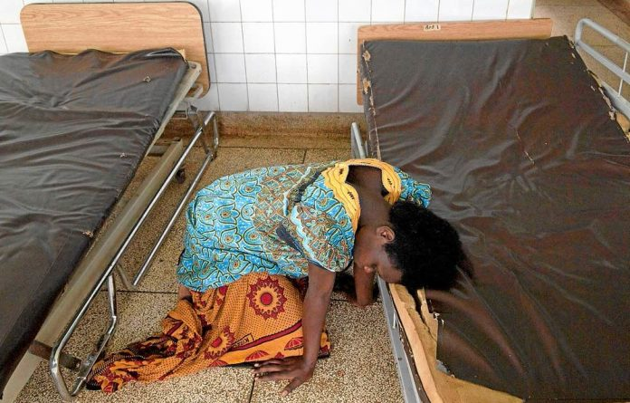 Helpless: A woman waits to be assisted by a midwife in the delivery room of a hospital in Uganda. Ugandan health workers tend to move abroad because there are no jobs at home.