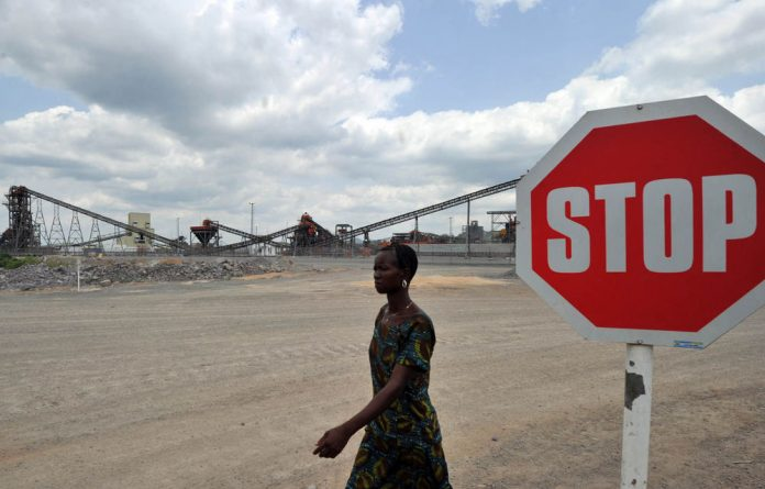 A woman walks past the crushing circuits at the diamond mining company Koidu Holdings plant