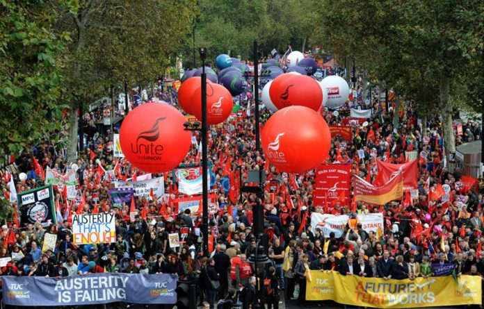 Demonstrators gather in central London as they prepare to march against the government's austerity policies and call for an alternative economic strategy that puts jobs and growth first.