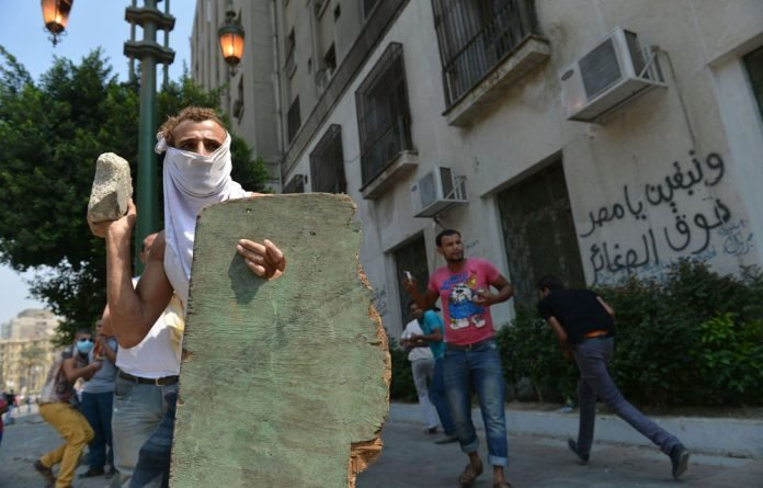 An Egyptian protester holds a makeshift shield as he throws a stone towards the riot police during clashes near the US embassy in Cairo.