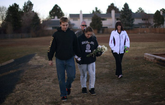 An Arapahoe High School student arrives with flowers for a prayer vigil at the school in Centennial