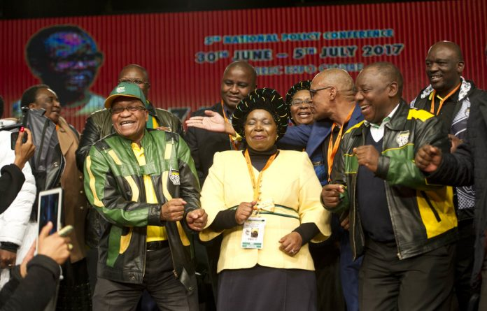 Smile for the camera: President Jacob Zuma shuffles along with his preferred successor Nkosazana Dlamini-Zuma and her rival for the position of ANC president