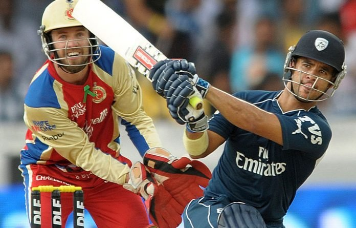 Deccan Chargers's Jean Paul Duminy bats as Royal Challengers Bangalore's AB de Villiers looks on during an IPL Twenty20 cricket match.