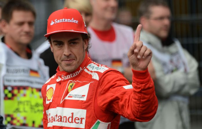 Ferrari's Fernando Alonso celebrates in the parc ferme after the qualifying session at the Hockenheimring circuit ahead of the German F1 GP.