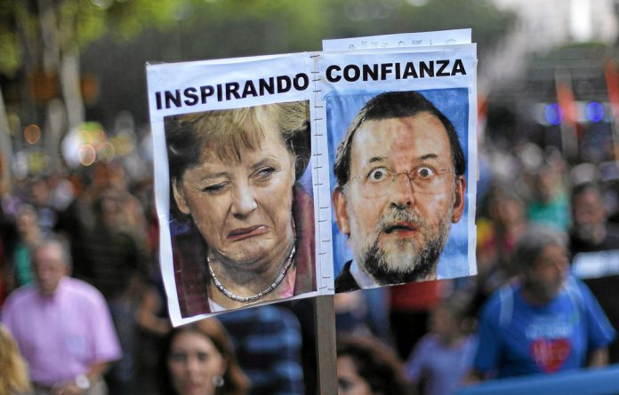 Spanish anti-austerity protesters hold a banner with the words 'inspiring confidence' and photos of German Chancellor Angela Merkel and Spanish Prime Minister Mariano Rajoy.