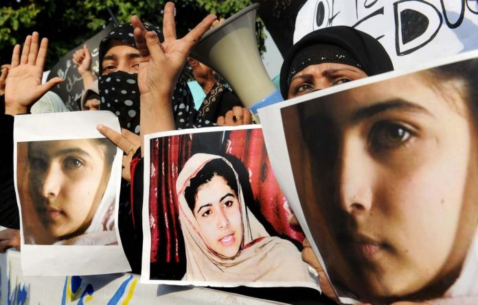 Pakistani Islamist activists carry photographs of gunshot victim Malala Yousafzai during a protest rally against her assassination attempt.