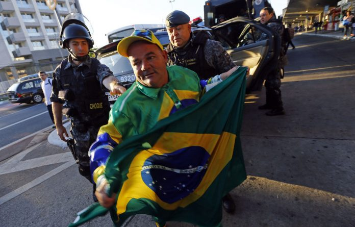 A man holds a Brazilian flag in front of two police officer outside Ana Rosa subway station during the fifth day of metro workers' protest.