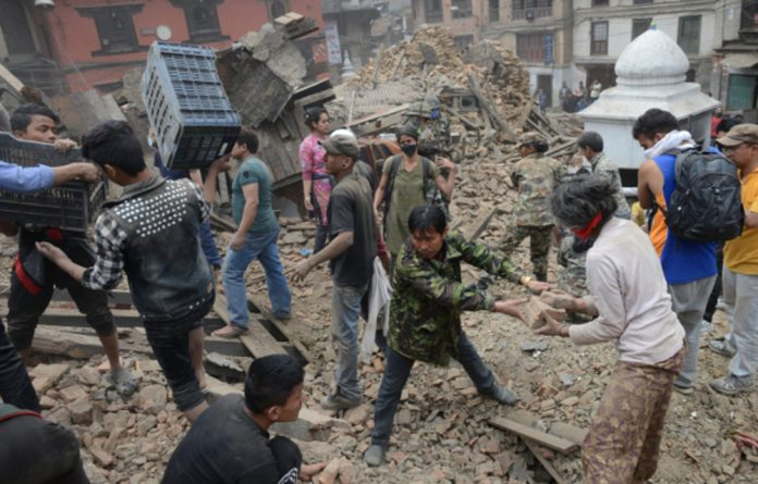 Rubble is cleared in Kathmandu's Durbar Square on Saturday. A massive 7.8 magnitude earthquake killed hundreds of people as it ripped through large parts of Nepal.
