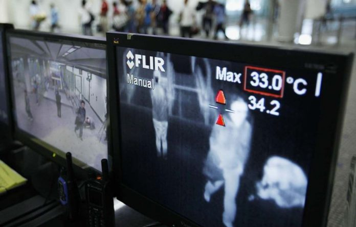 Monitors show the body heat of incoming passengers at a Hong Kong airport in 2009.