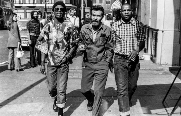 A photograph from 1973 shows playwright Athol Fugard flanked by Ntshona
