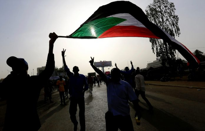 Sudanese demonstrators wave their national flag as they arrive for a protest rally demanding Sudanese President Omar Al-Bashir to step down outside the Defence Ministry in Khartoum