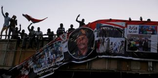 Protesters tear down a banner with a picture of Sudan's head of transitional council