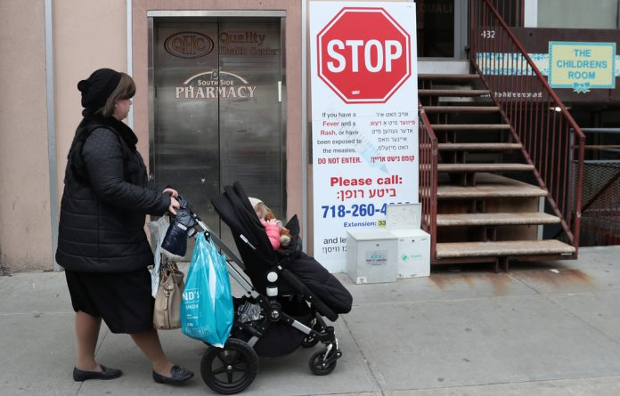 A sign warns people of measles in the ultra-Orthodox Jewish community of Williamsburg