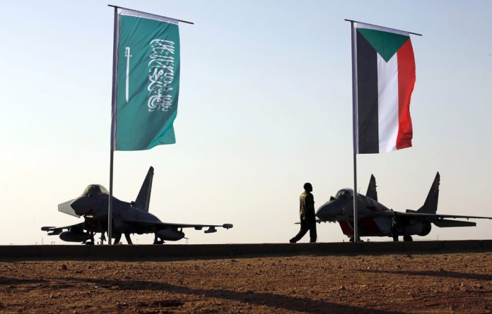 Military personnel walk past the flags of Saudi Arabia and Sudan during a training exercise between the Saudi Air Force and Sudanese Air Forces at Merowe Airport in Sudan.