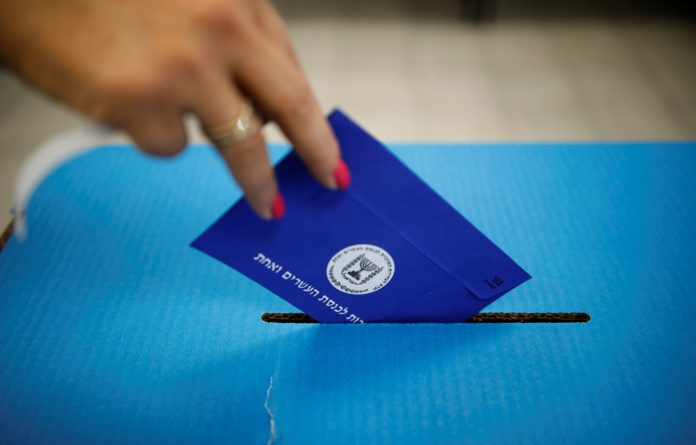 A women casts her vote in a ballot box as Israelis began voting in a parliamentary election