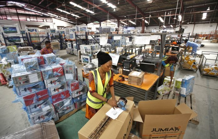 A worker packs goods in a Jumia Technologies AG distribution warehouse in Lagos