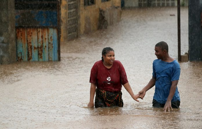 A man helps a woman through a flooded neighbourhood in the aftermath of Cyclone Kenneth