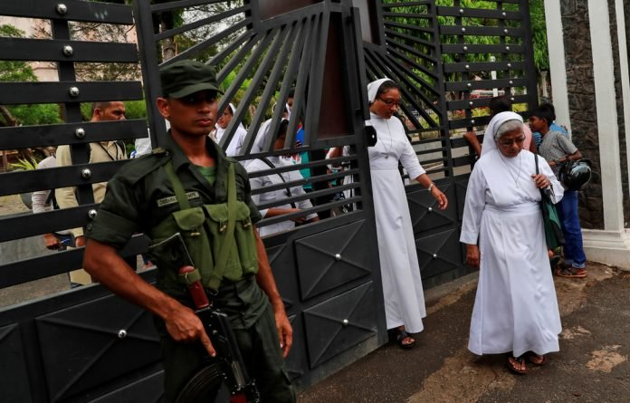 A soldier keeps guard as nuns walk out of St. Sebastian Church in Negombo