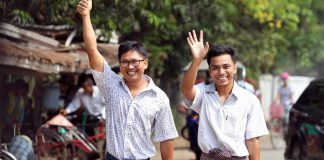 Reuters reporters Wa Lone and Kyaw Soe Oo gesture as they walk to Insein prison gate after being freed