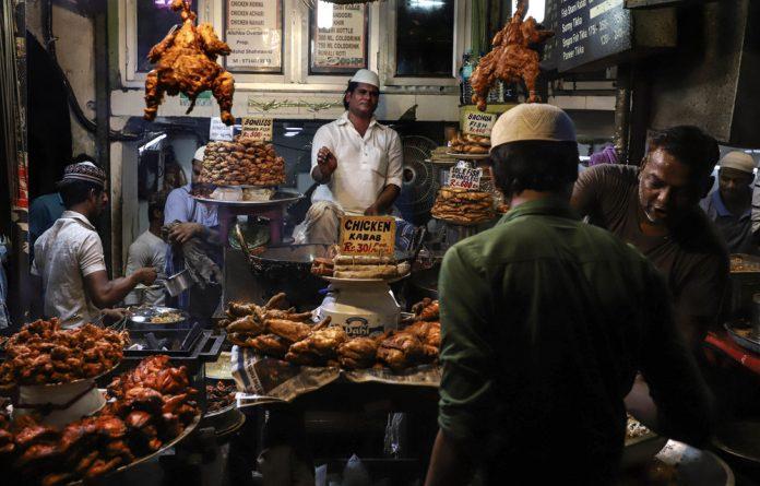 A vendor fries chicken pieces in Delhi.