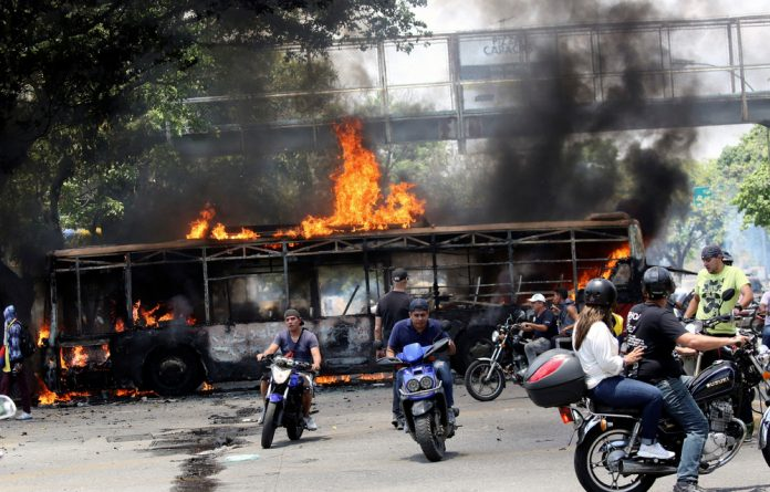 People drive their motorcycles near a burnt bus during anti-government protests