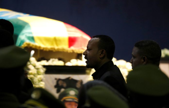 Ethiopia's Prime Minister Abiy Ahmed walks past the coffin of Army Chief of Staff Seare Mekonnen