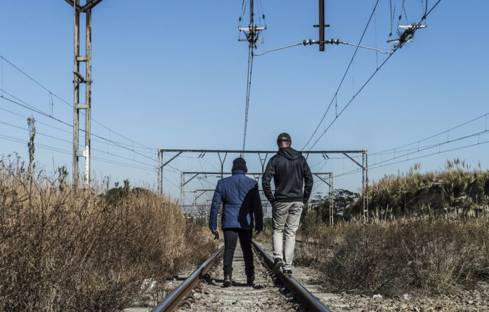 Security guards patrol Prasa rail tracks. Many of the guards who protect the rail agency's property are employed by outside companies but they would prefer to be permanent employees of Prasa.