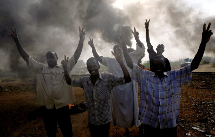 Sudanese protesters gesture as they chant slogans along a street and demanding that the country's Transitional Military Council hand over power to civilians in Khartoum