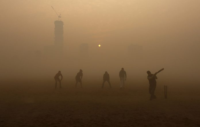 Boys play cricket in a public park amidst heavy fog on a cold winter morning in India.