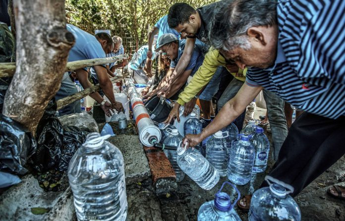 Drought equaliser: Cape Town residents last year queued to refill water bottles at Newlands Spring.