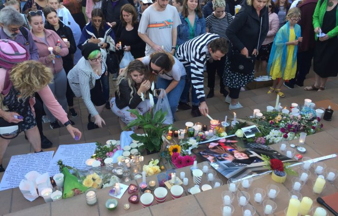 A woman comforts her friend at a vigil for murdered British backpacker Grace Millane in Wellington