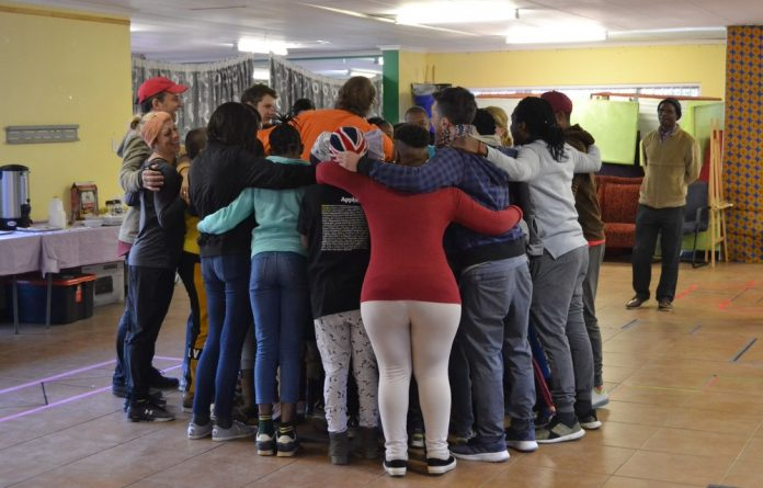 Youngsters huddle together in a group hug at Nkosi's Haven following their morning warm-up.
