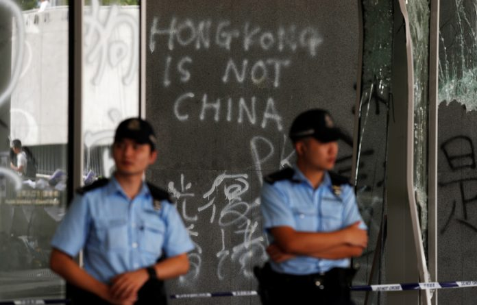 Police stand in front of graffiti on the walls of the Legislative Council