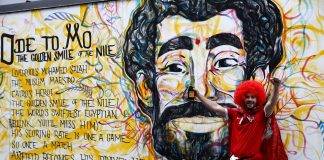 A fan poses in front of a mural picturing Liverpool's Mohamed Salah before the macth.